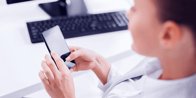 Mulher usando ferramentas de escolas pelo celular, sentada em uma mesa com um computador