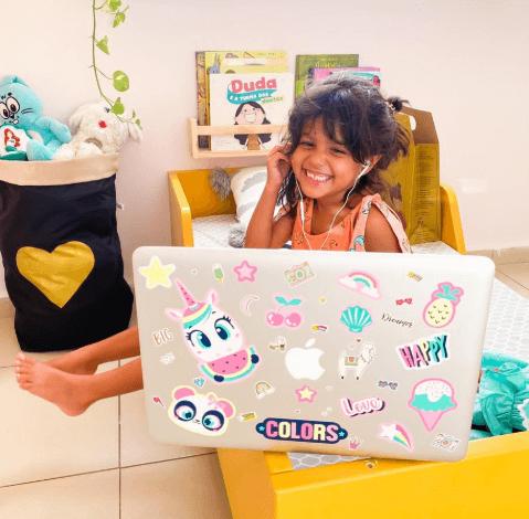 Menina estudando com notebook no quarto