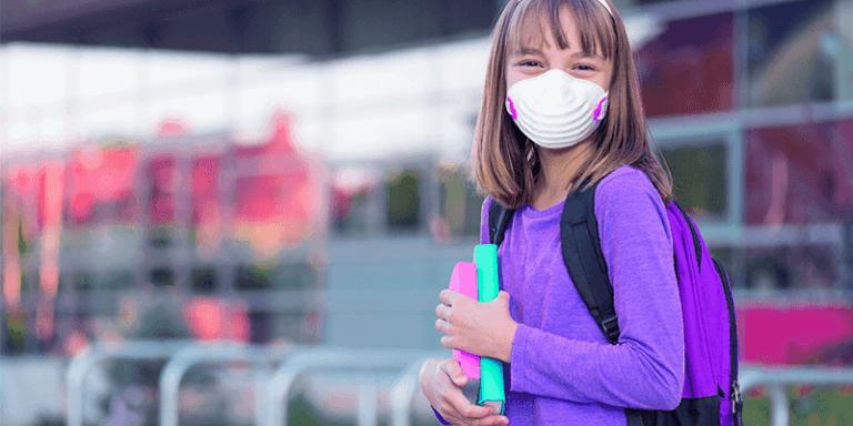 Menina de máscara e livros na mão no retorno às aulas