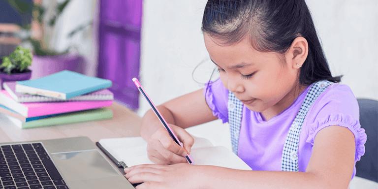 Aluna escrevendo em caderno, sentada na carteira para mostrar indicadores de desempenho