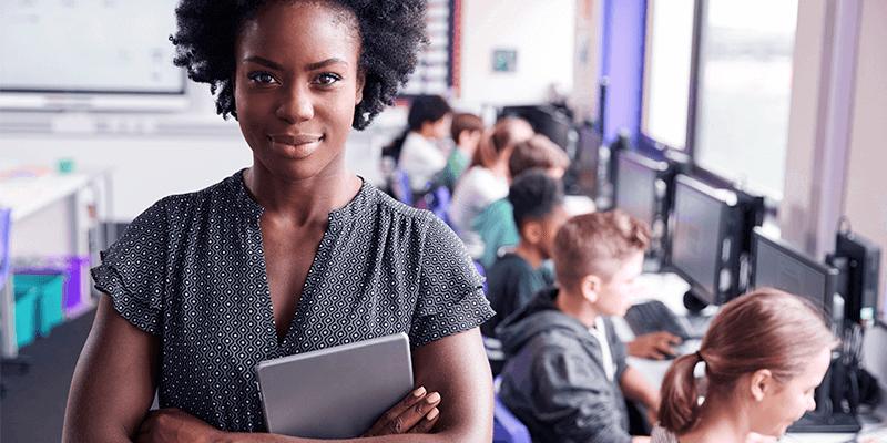 Professora com livro na sala de aula com alunos ao fundo exemplificando uma profissional com plano de carreira