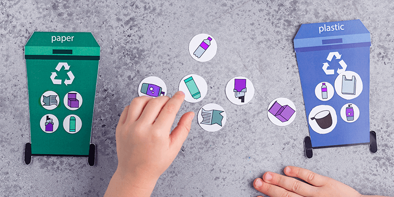 Visão de cima de mãos de criança brincando com papéis desenhados de duas lixeiras recicláveis e os lixos de cada uma para mostrar a sustentabilidade na escola dentro de casa