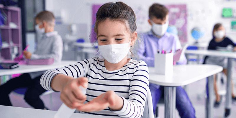 Menina de máscara sentada na carteira em volta às aulas e colocando álcool em gel nas mãos