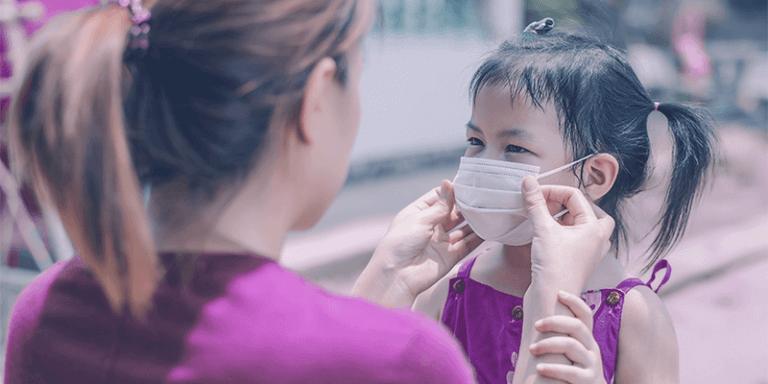 Adaptabilidade de professora colocando uma máscara em aluna