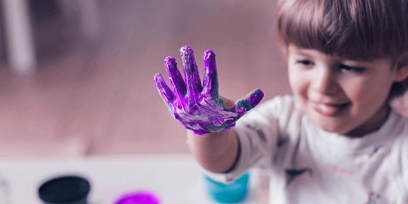 Criança com mão de cheia de tinta brincando com arte da Educação Infantil