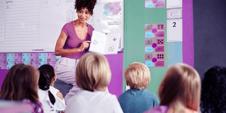 O que é storytelling: professora em sala de aula lendo livros para alunos