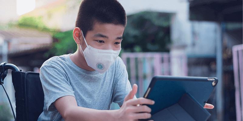 Alunos com necessidades especiais na retomada: aluno cadeirante de máscara e usando tablet