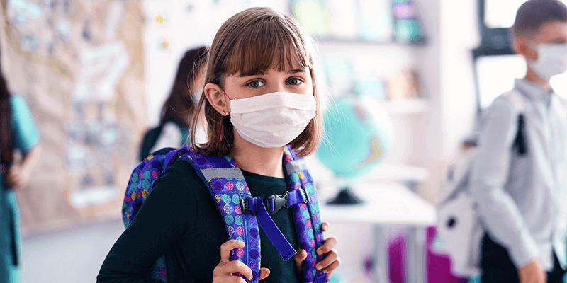 Aluna de máscara no retorno das aulas, com mochila na sala de aula