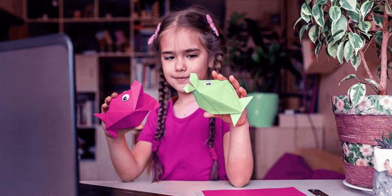 Menina fazendo atividades de Educação Infantil brincando com peixes de papel em frente ao notebook