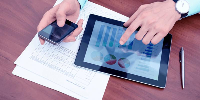 Campanha de rematrícula sendo planejada com papéis, tablet e celular mostrando gráficos