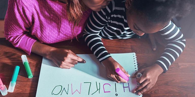 Alfabetização em casa com criança e mãe escrevendo letras em papel