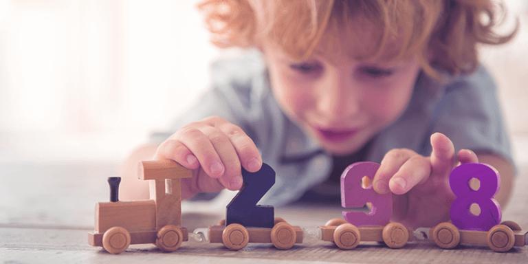 Criança brincando com jogos lúdicos e brinquedos de madeira