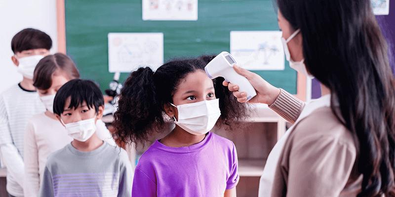 Aluna de máscara sendo testada com termômetro por professora no retorno das aulas