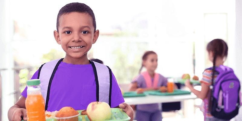 Aluno de mochila no refeitório, segurando bandeja com alimentos do cardápio infantil
