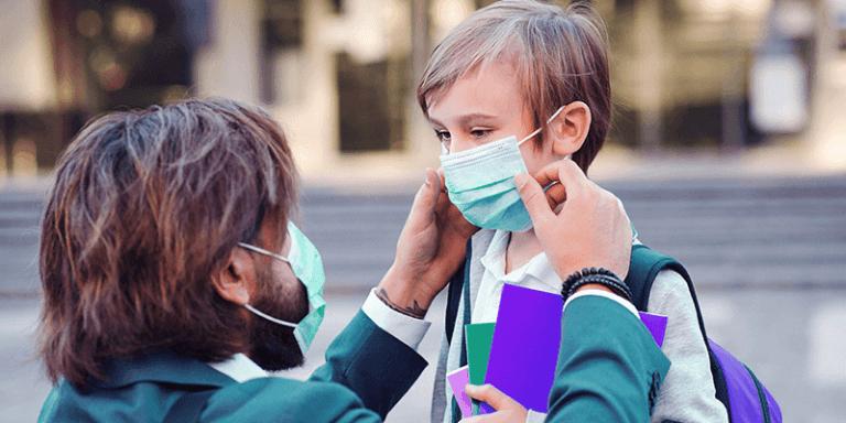 Pai ajustando máscara em filho para a escola