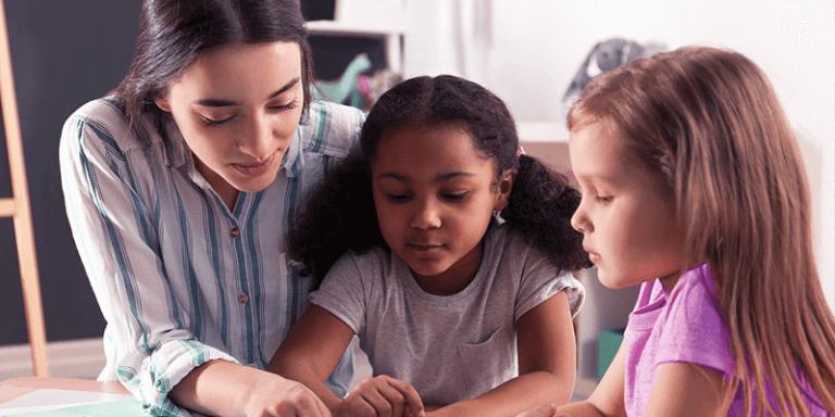 Professora auxiliando alunas em sala de aula na escola construtivista