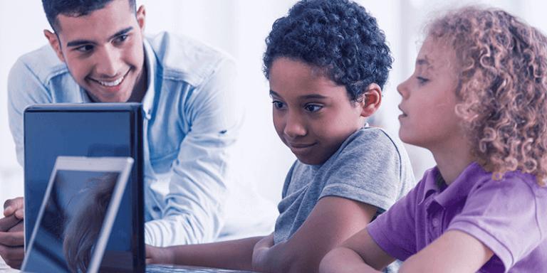 Alunos no computador com professor e aprendendo com gamificação