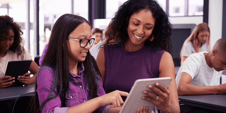 Professora e aluna usando tablet na sala de aula