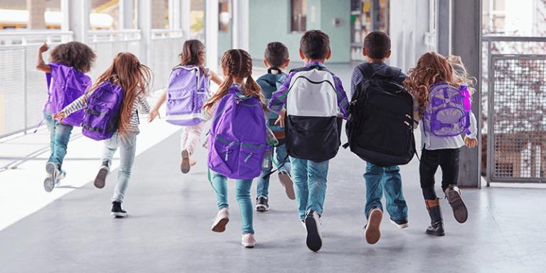 Alunos com mochilas correndo no corredor da escola no primeiro dia de aula