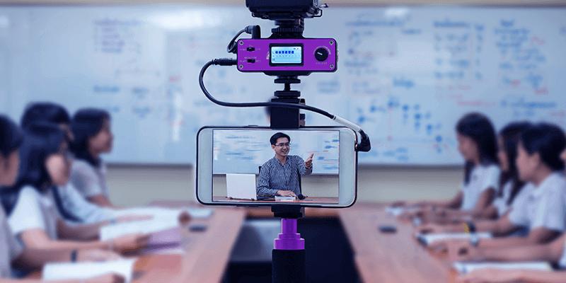 Tendências da educação: sala de aula com alunos e professor sendo gravado por celular em tripé para transmissão ao vivo