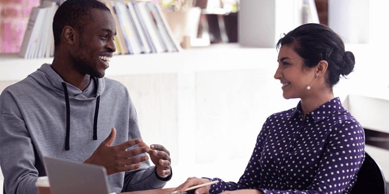 Gestão escolar: gestor e professor conversam na escola com notebook