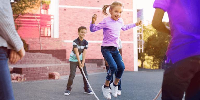 Crianças brincando com de pular corda no pátio da escola