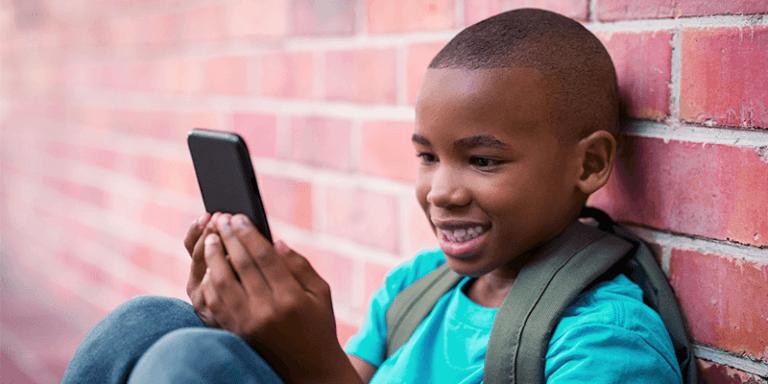 Tempo de tela: criança de mochila sorrindo e utilizando celular
