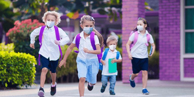 Alunos de máscara correndo na escola para volta às aulas 2021