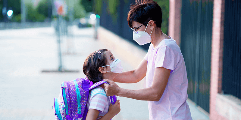 Mãe e filha de máscara na entrada da escola para volta às aulas presenciais