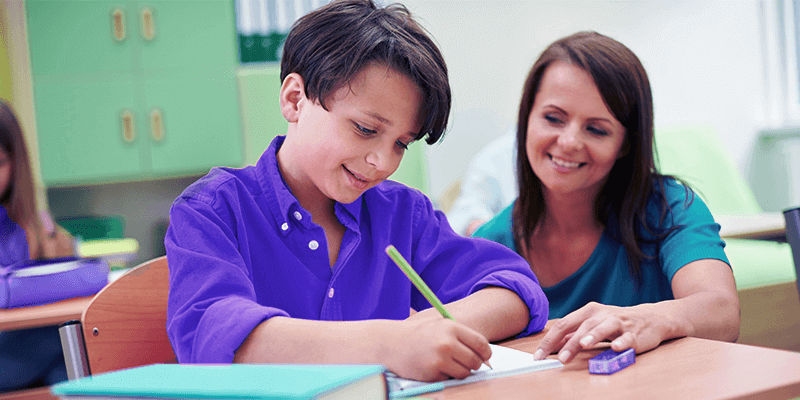 Professora ajudando aluno em apoio pedagógico