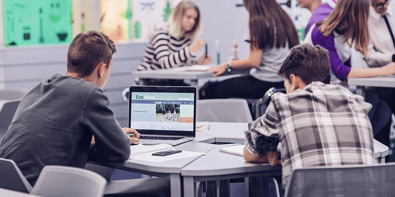 Alunos trabalhando em conjunto em sala de aula com mesa e notebooks, exemplo de interdisciplinaridade