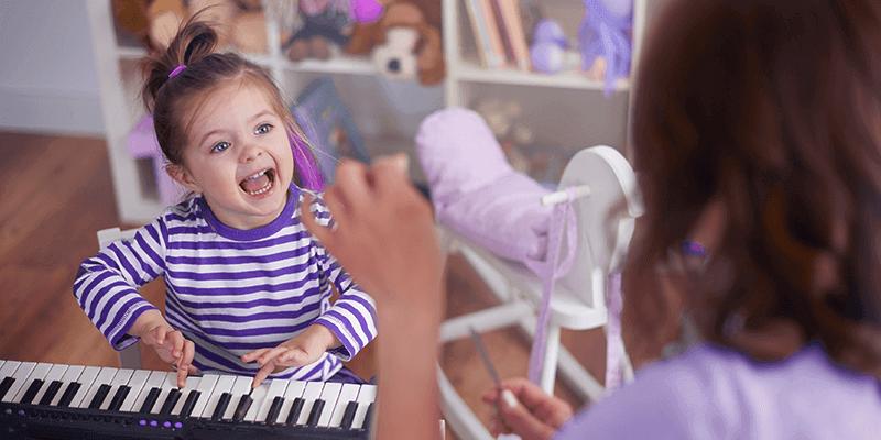 Menina criança tocando piano com ajuda de professora