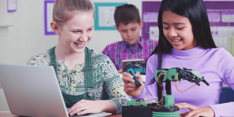 Alunas estudando em sala de aula com notebook e robóticas, tecnologias digitais