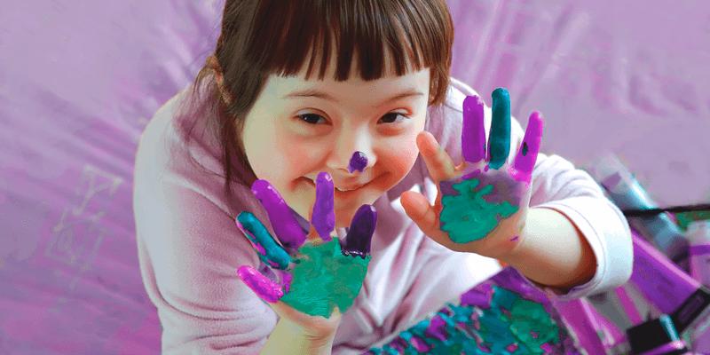 Criança com Síndrome de Down mostrando os dedos sujos de tinta, brincado de pintar e explorando a criatividade infantil