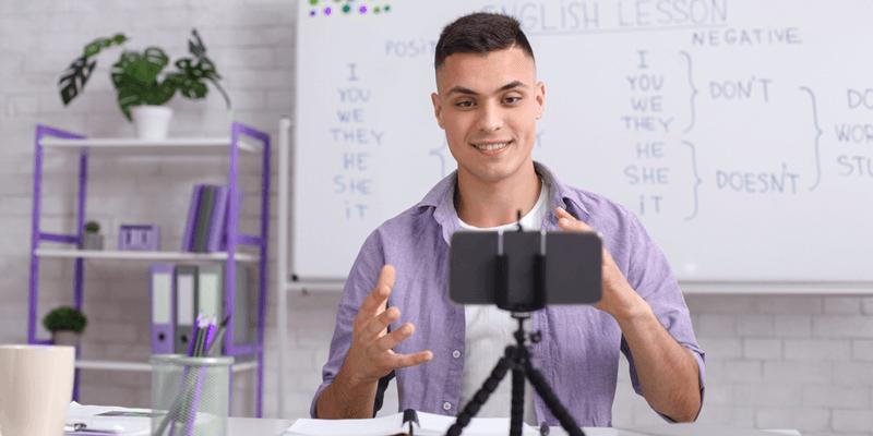Professor em sala de aula gravando aula pelo celular e usando ferramentas online