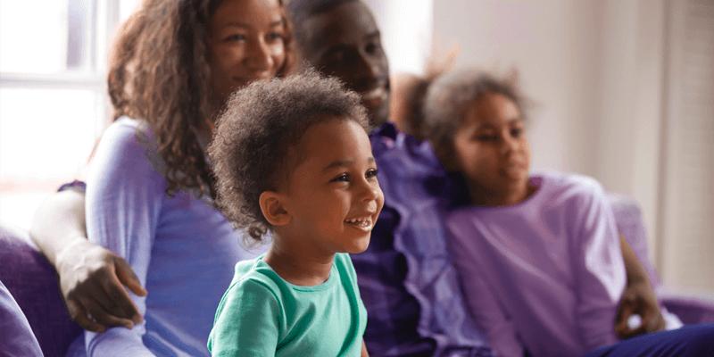Família sentada em sofá da sala assistindo filmes sobre autismo