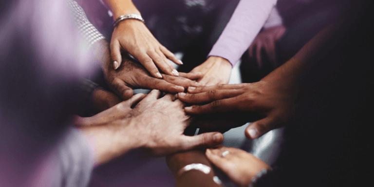 Várias mãos de diferentes raças unidas, representando a gestão democrática na escola