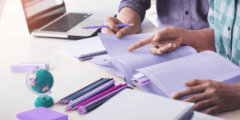 Mesa com papéis, lápis e notebook com mãos de pessoas fazendo planejamento escolar