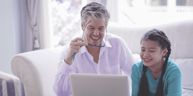 Aluna e pai estudando juntos em casa com notebook em aula online