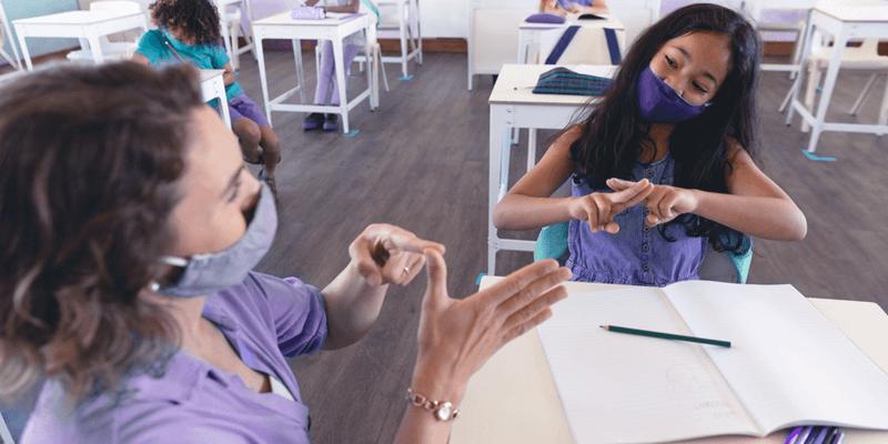 Aluna e professora de máscara conversando em Libras em atendimento educacional especializado