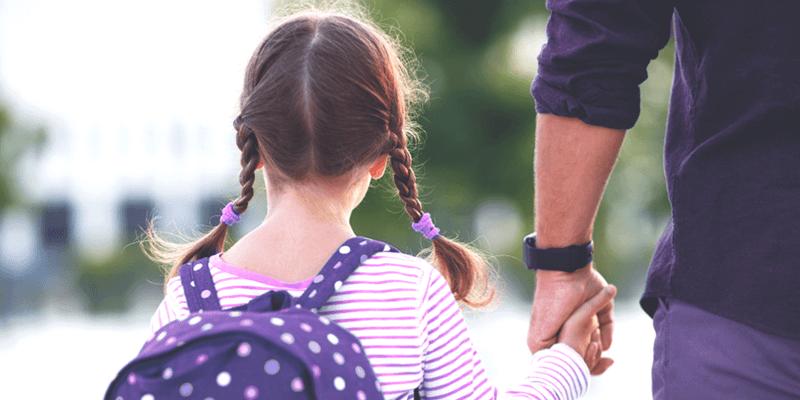 Criança de mochila de mãos dadas com pai à caminho da escola