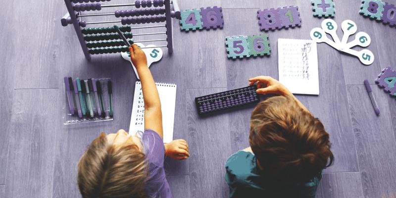 Alunos brincando no chão com ábaco e jogos de números
