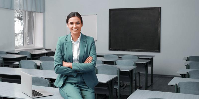 Gestora escolar apoiada em mesa na sala de aula