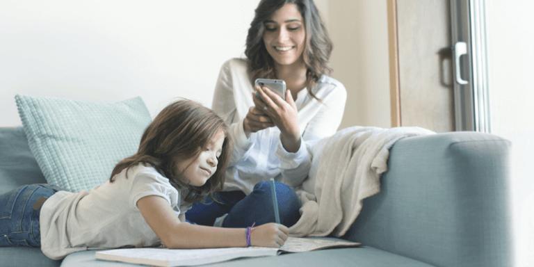 Mãe e filha na sala de casa fazendo tarefa e lendo comunicado escolar pelo celular