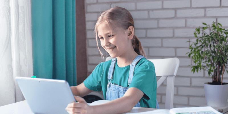 Criança fazendo leitura digital em tablet na sala de casa