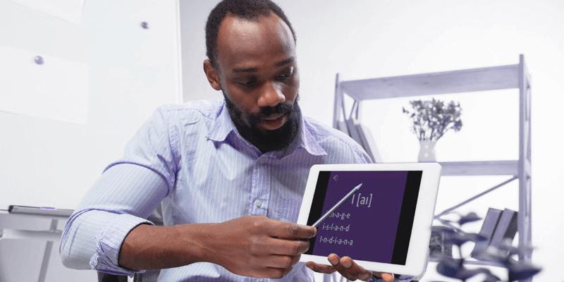 Professor em sala de aula mostrando conteúdo em tablet