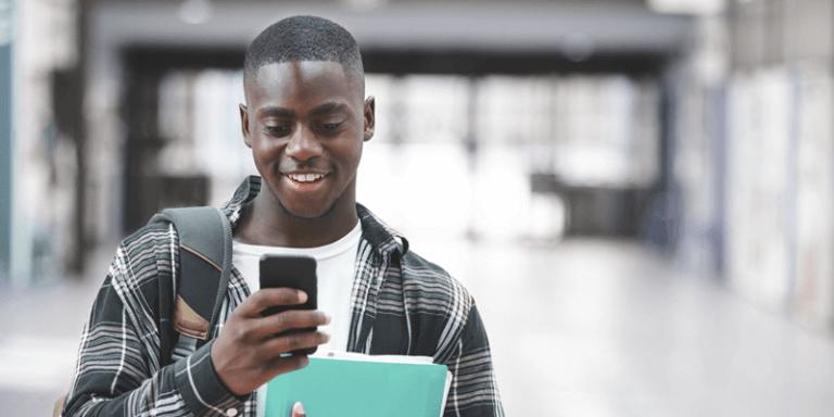 Aluno adolescente conferindo o celular no corredor da escola