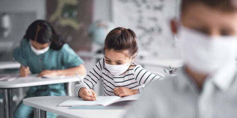 Sala de aula com crianças sentadas nas carteiras, estudando e usando máscaras