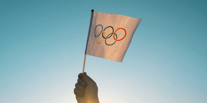 Imagem de uma mão segurando uma bandeira pequena das Olimpíadas com o céu ao fundo