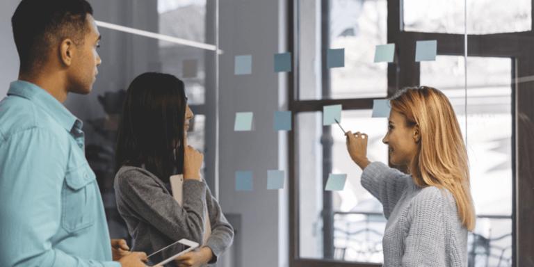 Pessoas em sala de reunião colando post-its em parede de vidro